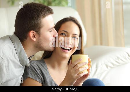 Glücklicher Ehemann küsst seine Frau im Wohnzimmer zu Hause. Glückliches Paar-Konzept - Stockfoto