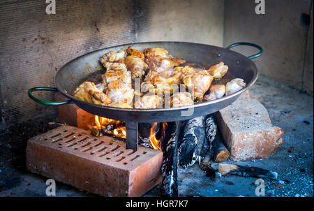 Kochen und eine traditionelle spanische Paella über offenem Feuer mit Feuerholz und Kohle. Hergestellt aus Hühner - Stockfoto