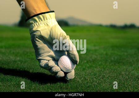 Hand mit einem Handschuh ist einen Golfball auf dem Boden platzieren. - Stockfoto