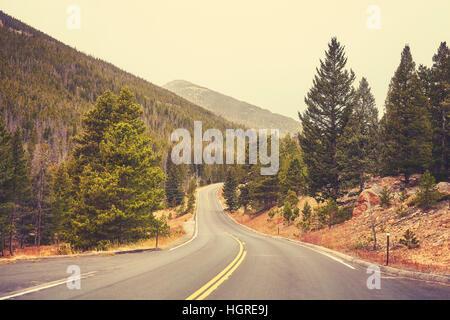 Retro-Farbe getönt leere Straße im Rocky Mountains National Park an einem bewölkten Tag, Colorado, USA. - Stockfoto