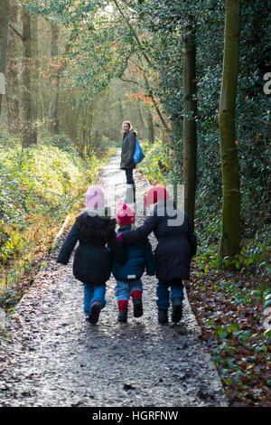 Mutter & 3 Kinder drei Kinder Töchter gehen / laufen auf schlammigen Weg / im Schlamm auf Gehweg Weg Fuß Weg Fußweg - Stockfoto