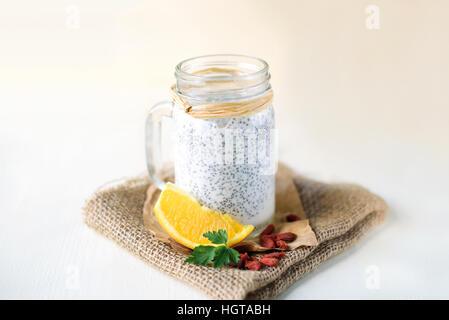 Chia Samen Pudding in einem Glas auf weißem Hintergrund aus Holz, verziert mit Orange und Goji Beeren - Stockfoto