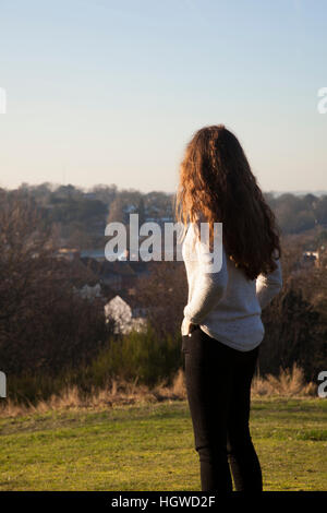 Junge Frau mit langen Haaren zurück zur Kamera stehen, Blick in die Ferne. Dreiviertel-Länge. - Stockfoto