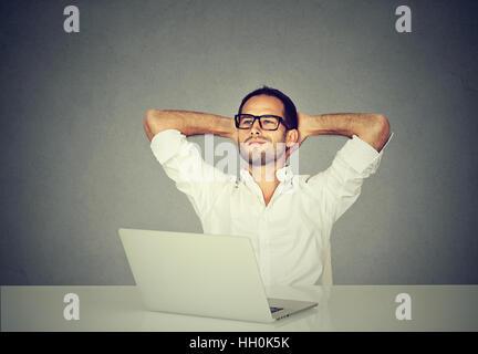 Lächelnd träumt Mann in Gläsern nachschlagen auf Laptop-Computer arbeiten. Glücklicher Kerl entspannen nach arbeiten - Stockfoto