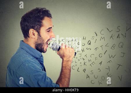 Junger Mann im Mikrofon singen mit Buchstaben aus seinem Mund kommt. Kommunikation, Information, Intelligenz-Konzept - Stockfoto