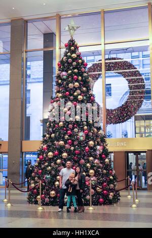 Familie posiert vor dem riesigen Weihnachtsbaum in der Lobby MetLife Building, NYC, USA - Stockfoto