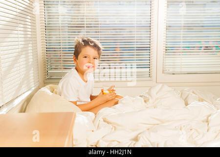 Kleiner Junge trinkt Orangensaft sitzen im Bett - Stockfoto