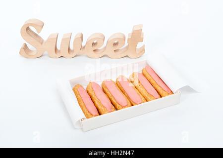 Offene Lieferung Pappschachtel mit sechs frischen rosa Muffins und hölzernen Wort süß auf weißem Hintergrund. Romantisches - Stockfoto