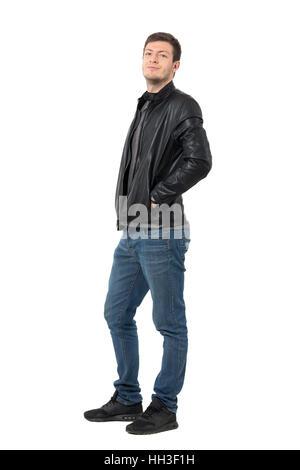 Seitenansicht des Jünglings lässig in Jeans und Lederjacke in die Kamera Grinsen. Ganzkörper-Länge-Porträt isoliert - Stockfoto