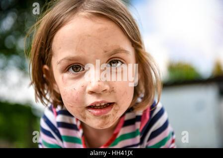 Kleines Kind mit dreckiges Gesicht von draußen spielen im Dreck und Schlamm. Spiele in der Natur, gesunde Kinder - Stockfoto