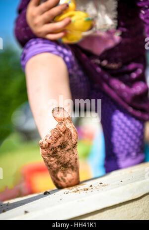 Kind zeigt schmutzige Füße im Schlamm zu spielen. Spiel draußen in der Natur. - Stockfoto