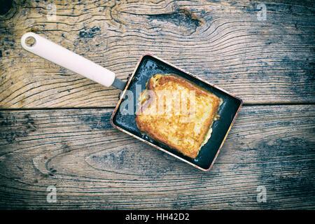 Eggy Brot / Toast Französisch in einer rechteckigen Bratpfanne auf Holz. Vintage Retro-Filter angewendet