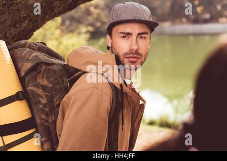 Junge bärtige Mann Reisenden mit Rucksack ansehen unter riesigen Baum in der Nähe von Fluss und Blick auf unscharfen - Stockfoto