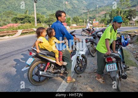 Vater den Transport von drei kleinen Kindern, ländlichen Highway angehalten, ein Gespräch mit Bauernmarkt, Yamaha - Stockfoto