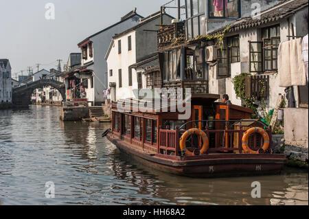 Traditionelles Boot vor einer Residenz in Suzhou, China. Die Architektur rund um die Kanäle in Suzhou, mit Objekten - Stockfoto