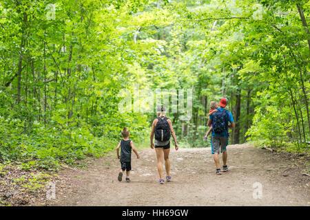 Paar Leute zusammen im Wald wandern hinunter einen Feldweg an einem schönen Sommertag. Grünen Blätterdach der Bäume - Stockfoto