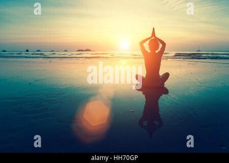 Silhouette Frau Yoga am Meer Strand bei Sonnenuntergang. - Stockfoto