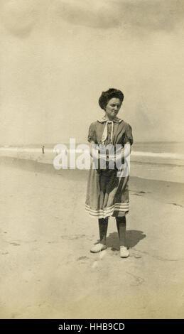 Antik 1908 Foto, Frau am Strand im viktorianischen Stil Badeanzug. Ort: New England, USA. QUELLE: ORIGINAL FOTOABZUG. - Stockfoto