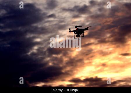 Die Drohne hebt ab, als die Sonne untergeht, so dass dem Bild eine leuchtende Orange mit dunklen Wolken, die Verbesserung - Stockfoto