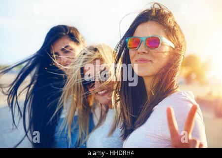 Hübsche junge Frau wirft Finger als Zeichen des Friedens stehen neben Freunde - Stockfoto