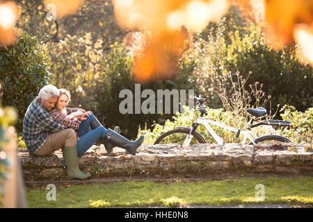 Zärtlich umarmt auf Steinmauer im Herbst Park paar - Stockfoto