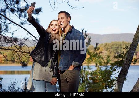 Zwei Menschen, Mann und Frau unter einem Selfie am Ufer eines Sees im Herbst. - Stockfoto
