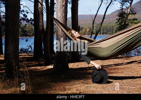 Eine Frau in einer Hängematte entspannen, unter den Kiefern an einem See liegen. - Stockfoto