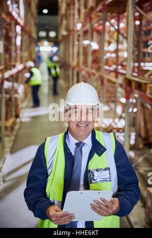 Porträt lächelnden Manager mit Zwischenablage im Auslieferungslager - Stockfoto