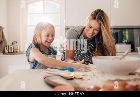 Fröhliches junges Mädchen mit ihrer Mutter Teig. Mutter und Tochter in Küche backen.