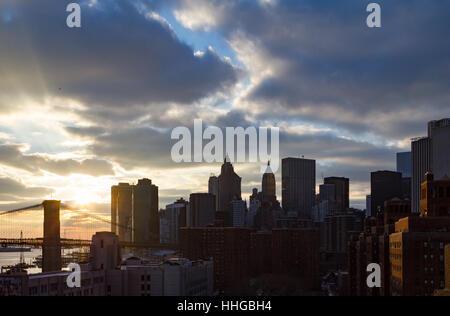 NYC Sonnenuntergang hinter der Skyline der Innenstadt Wolkenkratzer und die Brooklyn Bridge in Manhattan, New York - Stockfoto