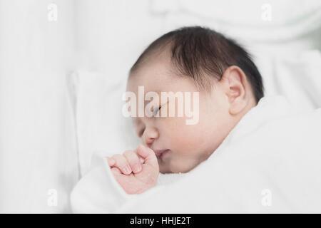 Asiatische neugeborenes Baby junge in einer weißen Decke schlafen. 2 Tage neugeborenes Baby Boy. - Stockfoto