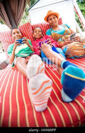 Porträt von schwarzen Mutter und zwei Söhne, die Nutzung von Mobiltelefonen im freien - Stockfoto