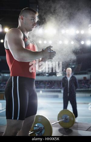 Trainer beobachten männliche Gewichtheber Auftragen von Kreide Puder, Hände an der Hantel - Stockfoto