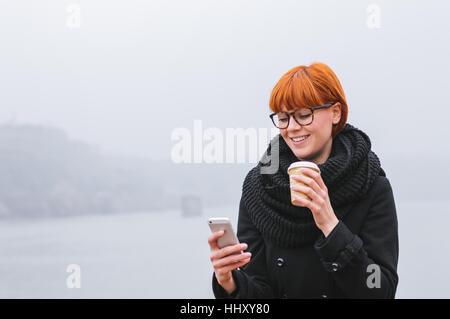 Junge, moderne Geschäftsfrau. Porträt des jungen Mädchens, das Smartphone überprüft. - Stockfoto