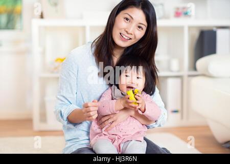 Mit ihrer niedlichen kleinen Kleinkind Tochter zu Hause ziemlich glücklich japanische Mutter spielen - Stockfoto