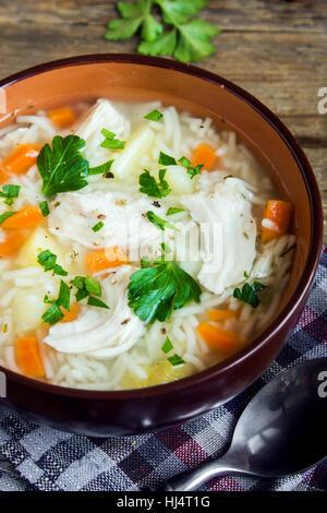 Hühnersuppe mit Nudeln und Gemüse in Schüssel über rustikalen hölzernen Hintergrund - hausgemachte gesunde Mahlzeit - Stockfoto