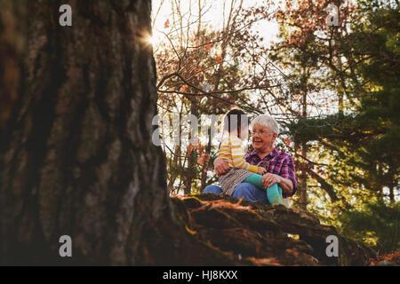 Großmutter und Enkelin sitzt im Wald sprechen - Stockfoto