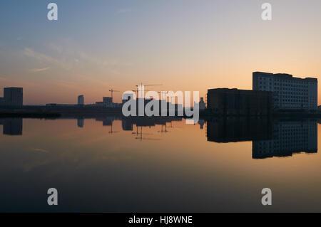Royal Victoria Docks, London UK, in der Dämmerung, mit Reflexionen und Krane - Stockfoto