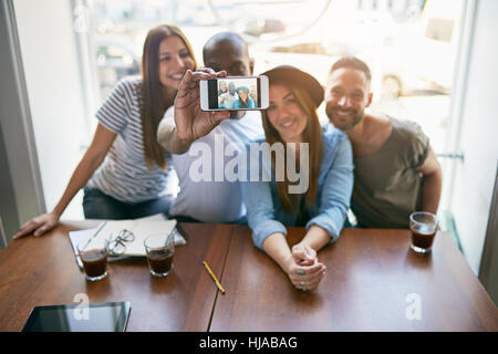 Gruppe von vier jungen Leuten am Tisch sitzen und takin Selfie mit Smartphone gegen Fenster. - Stockfoto