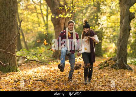 Junges Paar zu Fuß durch Wald, Hände halten, Lächeln - Stockfoto