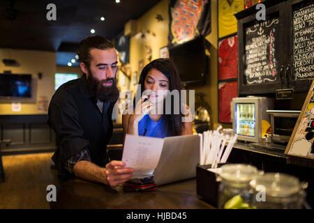 Junges Paar Lesung Menü im Wirtshaus Tisch - Stockfoto