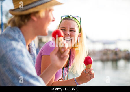 Junges Paar, lachen und essen Eiscreme-Kegel am Wasser, Mallorca, Spanien - Stockfoto