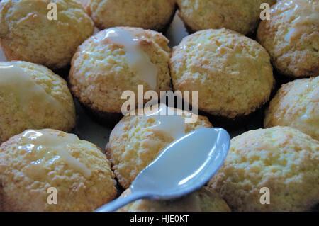 Ein Silberlöffel Glasur über Zitrone Mohnöl Muffins verteilen. - Stockfoto
