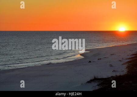Eine leuchtende orange Sonne über den Ozean in Perdido Key, in der Nähe von Pensacola. Stockfoto