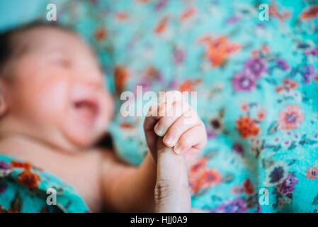 Neugeborenes Mädchen mit Mutters finger - Stockfoto