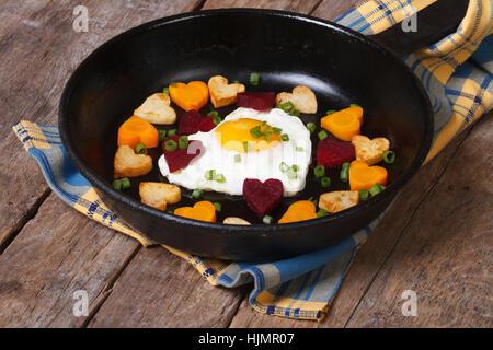 Spiegelei in Form Herzen auf Pfanne und Herzen, Karotten, Rüben und Kartoffeln - Stockfoto
