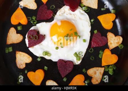 Herzen von Karotten, Kartoffeln, Rüben und Eiern in eine Pfanne geben-Makro. Ansicht von oben - Stockfoto