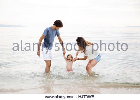 Eltern spielen mit ihren kleinen Mädchen im Meer - Stockfoto