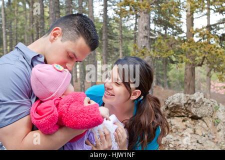 Eltern spielen mit und küssen Babymädchen - Stockfoto