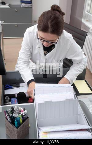 Arzt Sortierung Papierkram - Stockfoto